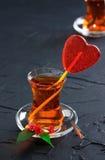 Tasse en verre avec un coeur de thé et de sucrerie Photographie stock libre de droits