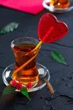 Tasse en verre avec un coeur de thé et de sucrerie Images libres de droits