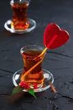 Tasse en verre avec un coeur de thé et de sucrerie Photo stock