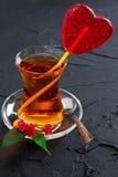 Tasse en verre avec un coeur de thé et de sucrerie Photos stock