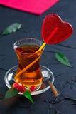 Tasse en verre avec un coeur de thé et de sucrerie Photos libres de droits