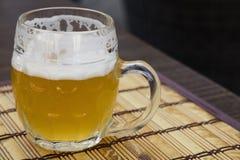 Tasse en verre de bière non filtrée de weizen sur la table Photos libres de droits
