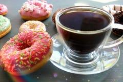 Tasse en verre de café chaud sur une table noire entourée par les butées toriques colorées photographie stock libre de droits