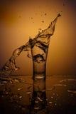 Tasse en verre de explosion avec de l'eau se brisant au-dessus du fond orange Image libre de droits