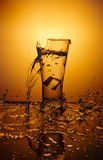 Tasse en verre de explosion avec de l'eau se brisant au-dessus du fond orange Photographie stock
