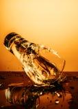 Tasse en verre de explosion avec de l'eau se brisant au-dessus du fond orange Photos stock
