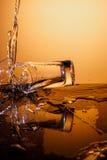 Tasse en verre de explosion avec de l'eau se brisant au-dessus du fond orange Images libres de droits