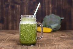 Tasse en verre de secousse de smoothie de jus d'aneth, brocoli, banane sur le fond en bois, fin  Photo libre de droits