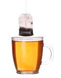Tasse en verre de thé avec le sachet à thé d'isolement sur le blanc Images stock