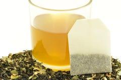 Tasse en verre de thé avec quelques feuilles de thé sèches Photos libres de droits