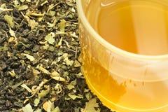Tasse en verre de thé avec quelques feuilles de thé sèches Images libres de droits