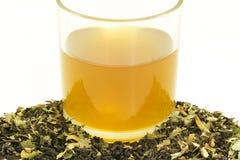 Tasse en verre de thé avec quelques feuilles de thé sèches Image libre de droits