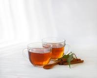 Tasse en verre de thé noir avec des bâtons de cannelle Photographie stock