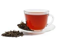 Tasse en verre de thé sur la soucoupe avec les feuilles sèches du thé vert sur le blanc Photos stock