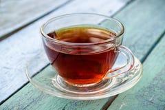 Tasse en verre de thé sur la vieille surface en bois Images stock