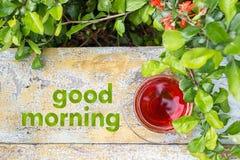 Tasse en verre de thé sur une surface en bois, herbe verte autour Fleurs oranges rouges Images stock