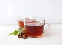 Tasse en verre de thé vert avec des bâtons de cannelle Images libres de droits