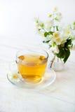 Tasse en verre de thé vert avec le bouquet du jasmin Photographie stock libre de droits
