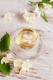 Tasse en verre de thé vert avec le jasmin sur le fond en bois Photo libre de droits