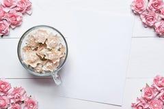 Tasse en verre pleine des roses blanches avec la feuille de papier blanc et le RO rose Photographie stock libre de droits