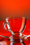 Tasse en verre transparente vide sur le fond rouge Photographie stock