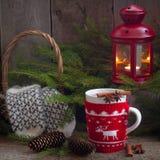 Tasse enveloppée tricotée faite main de Noël avec le thé, la lanterne ligntning rouge et les mitaines de laine Photographie stock libre de droits
