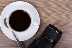 Tasse et appareil-photo de café sur une surface en bois Image stock