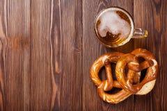 Tasse et bretzel de bière sur la table en bois Images libres de droits