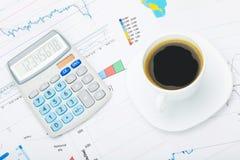 Tasse et calculatrice de café au-dessus de carte du monde et de documentation financière - fermez-vous vers le haut du tir de stu photo stock