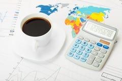Tasse et calculatrice de café au-dessus de carte du monde et de quelques diagrammes financiers photographie stock