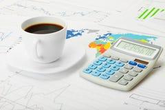 Tasse et calculatrice de café au-dessus de carte du monde et de quelques diagrammes financiers - concept d'affaires Image stock