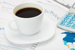 Tasse et calculatrice de café au-dessus de carte du monde et de quelques diagrammes financiers - concept d'affaires photo libre de droits