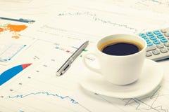 Tasse et calculatrice de café au-dessus de carte du monde et de quelques diagrammes financiers Image filtrée : effet de vintage t Photos libres de droits