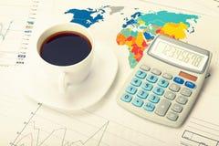 Tasse et calculatrice de café au-dessus de carte du monde et de quelques diagrammes financiers Image filtrée : effet de vintage t photos stock