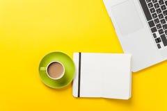 Tasse et carnet près de comuter d'ordinateur portable Photo stock