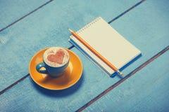 Tasse et crayon avec le carnet Photographie stock