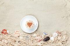 Tasse et filet avec des coquilles sur le sable Image libre de droits