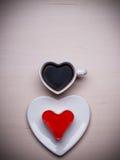Tasse et gâteau de café en forme de coeur sur la surface en bois Image stock
