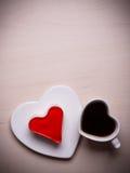 Tasse et gâteau de café en forme de coeur sur la surface en bois Photos stock