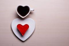 Tasse et gâteau de café en forme de coeur sur la surface en bois Images stock