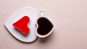 Tasse et gâteau de café en forme de coeur sur la surface en bois Photo stock