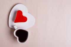 Tasse et gâteau de café en forme de coeur sur la surface en bois Image libre de droits