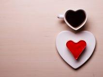 Tasse et gâteau de café en forme de coeur sur la surface en bois Photo libre de droits