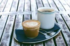 Tasse et gâteau de café sur une table en bois de vintage Concept de hippie Boisson de femme un café Tasses d'americano et de crèm Photos stock
