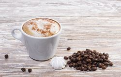 Tasse et grains de café blancs sur le fond en bois photos stock