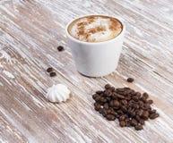 Tasse et grains de café blancs sur le fond en bois images stock