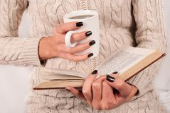 Tasse et livre de thé dans des mains de fille avec les clous noirs Photographie stock