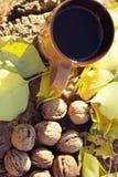 Tasse et noix sur un tronçon pendant l'automne Image stock
