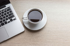 Tasse et ordinateur portable de café blanc sur la vue supérieure en bois de table Image libre de droits