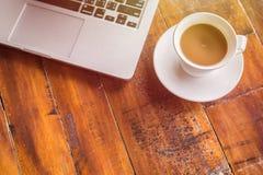 Tasse et ordinateur portable de café blanc sur la vue supérieure en bois de table Images libres de droits
